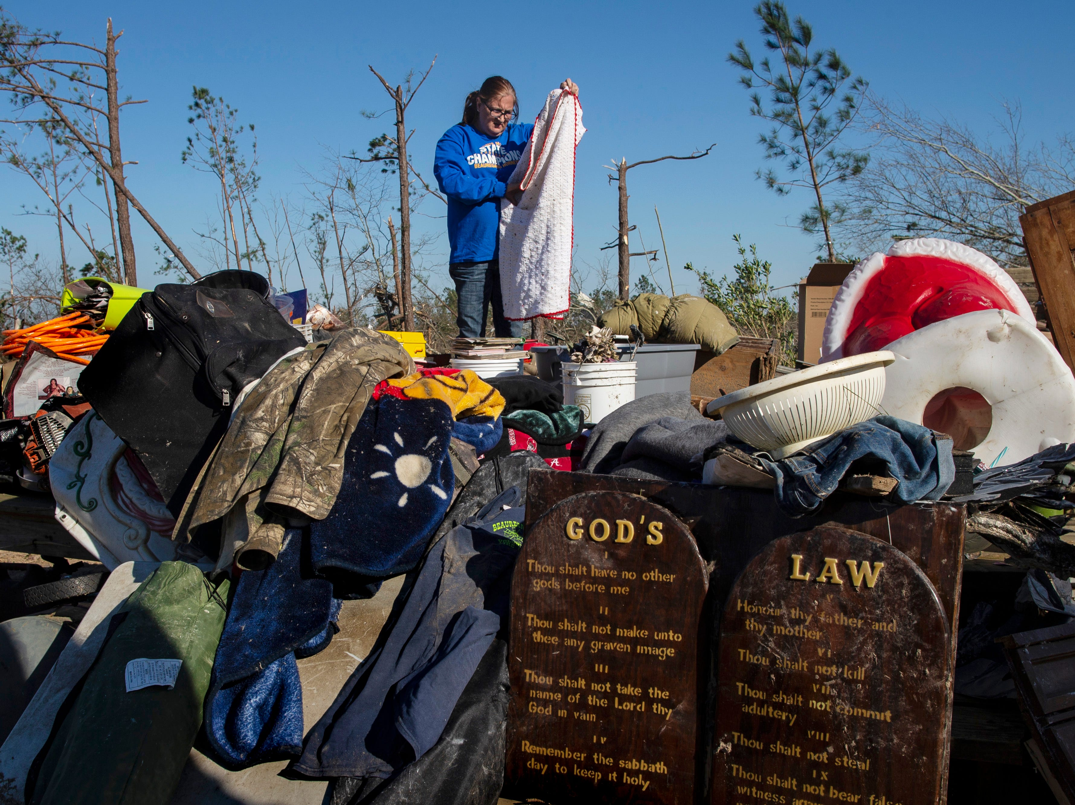 """Misha Cooley helps her sister-in-law, Susanne Polk, search for items after her trailer was destroyed in Beauregard, Ala. on March 6, 2019. """"God's law survived, just like his word survived,"""" Polk said. """"I just praise that he kept me safe."""""""