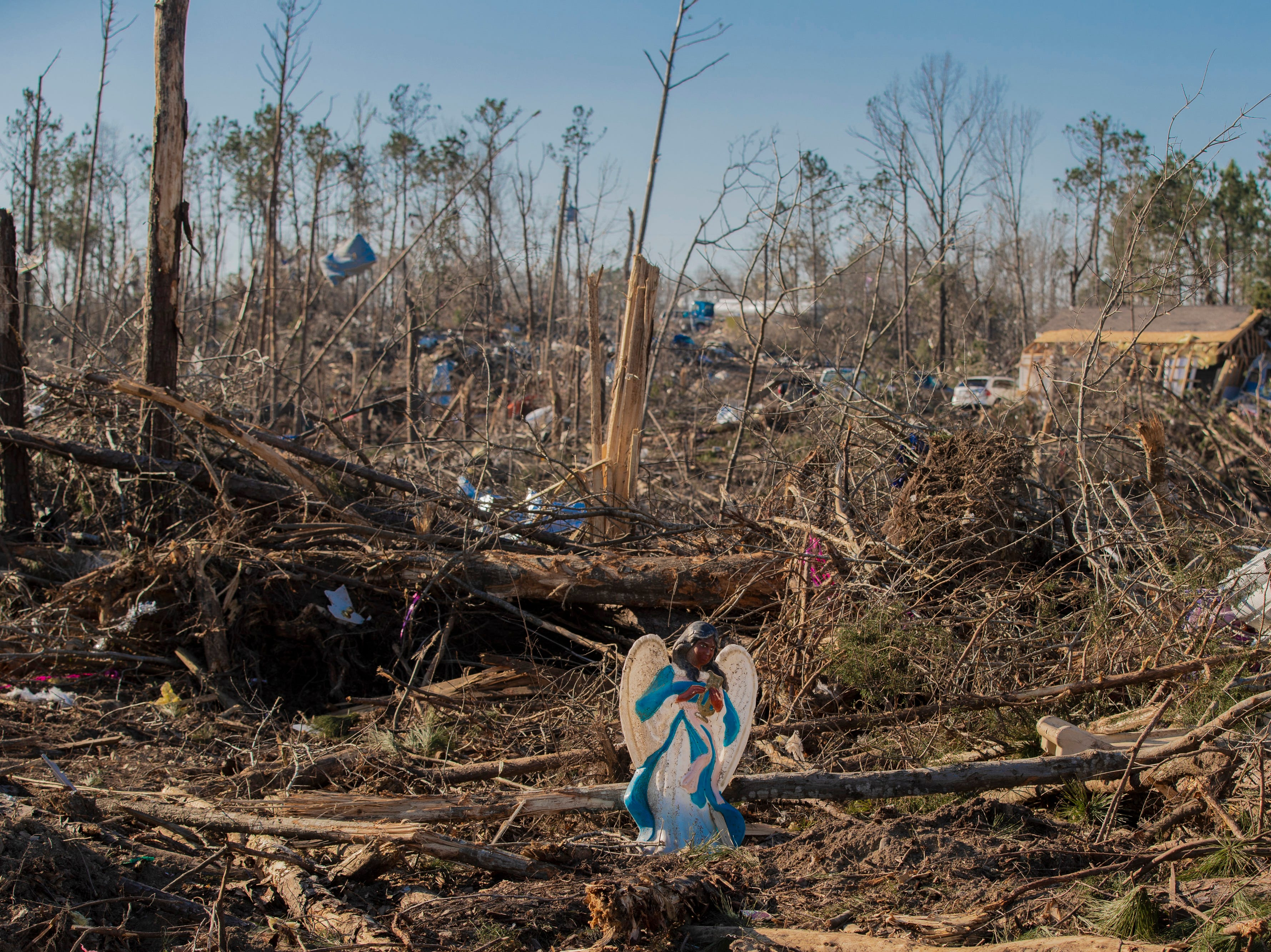 A plastic angel sits propped up among the broken trees and debris in Beauregard, Ala. on March 6, 2019.