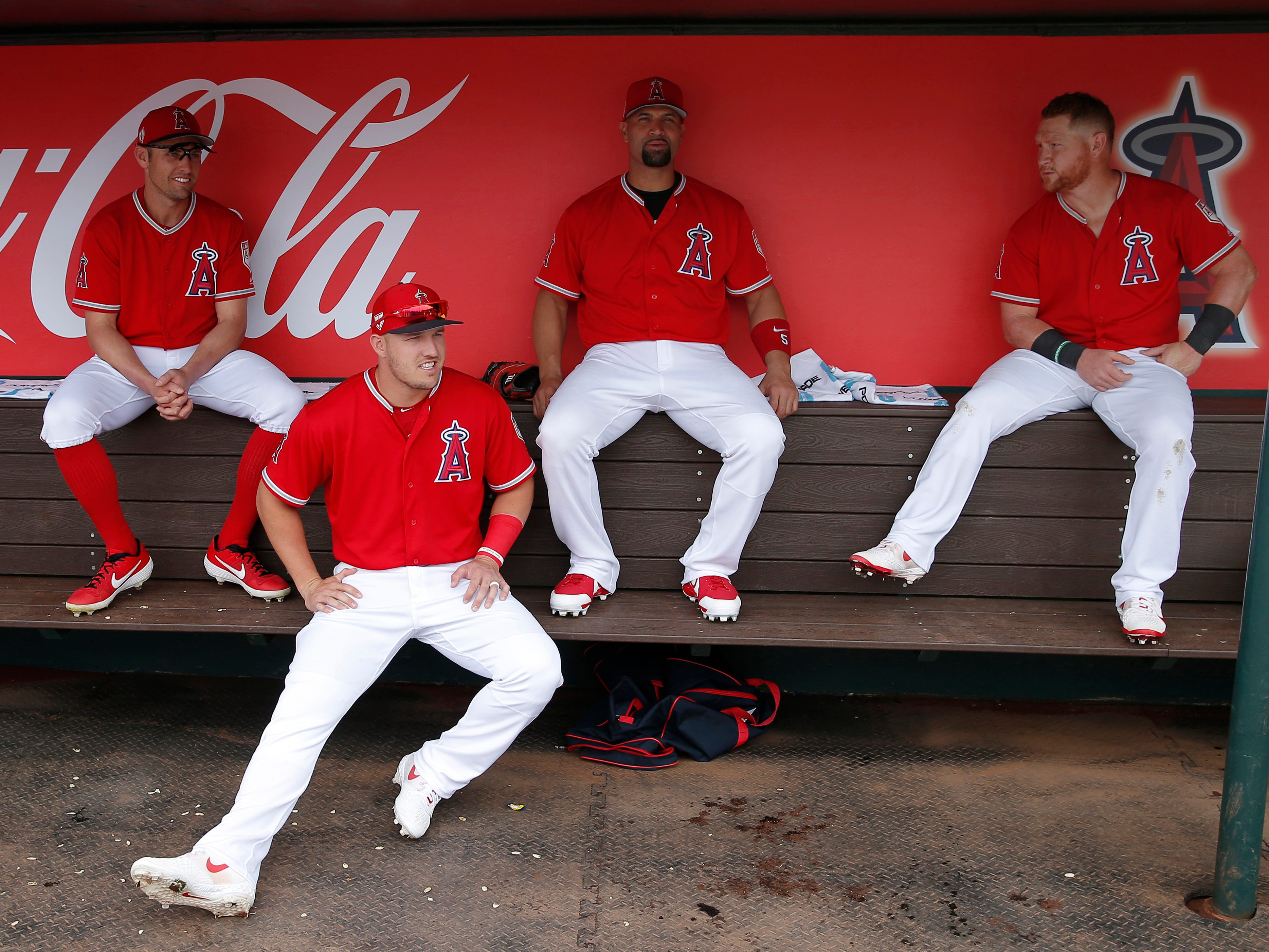 March 7: Angels' Peter Bourjos (left), Mike Trout (second from left), Albert Pujols (second from right) and Kole Calhoun (right) sit in the dugout before a spring game.