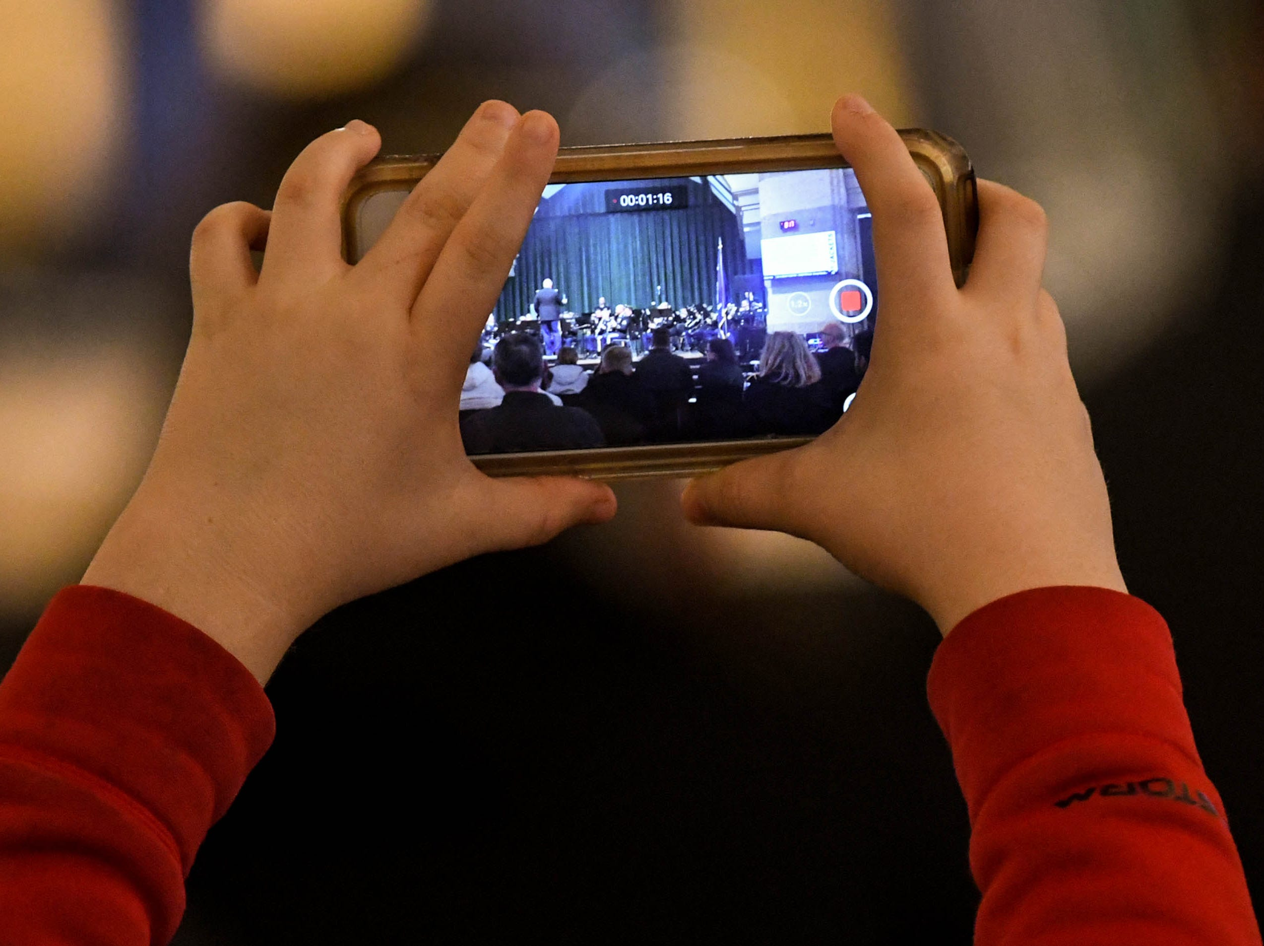 "A child holds up an iPhone to record video of SSG Chris Fairley singing ""God Bless the USA"" by Lee Greenwood, a solo with the 282d U.S. Army Band during a free concert at T.L. Hanna High School in Anderson Thursday, March 7."