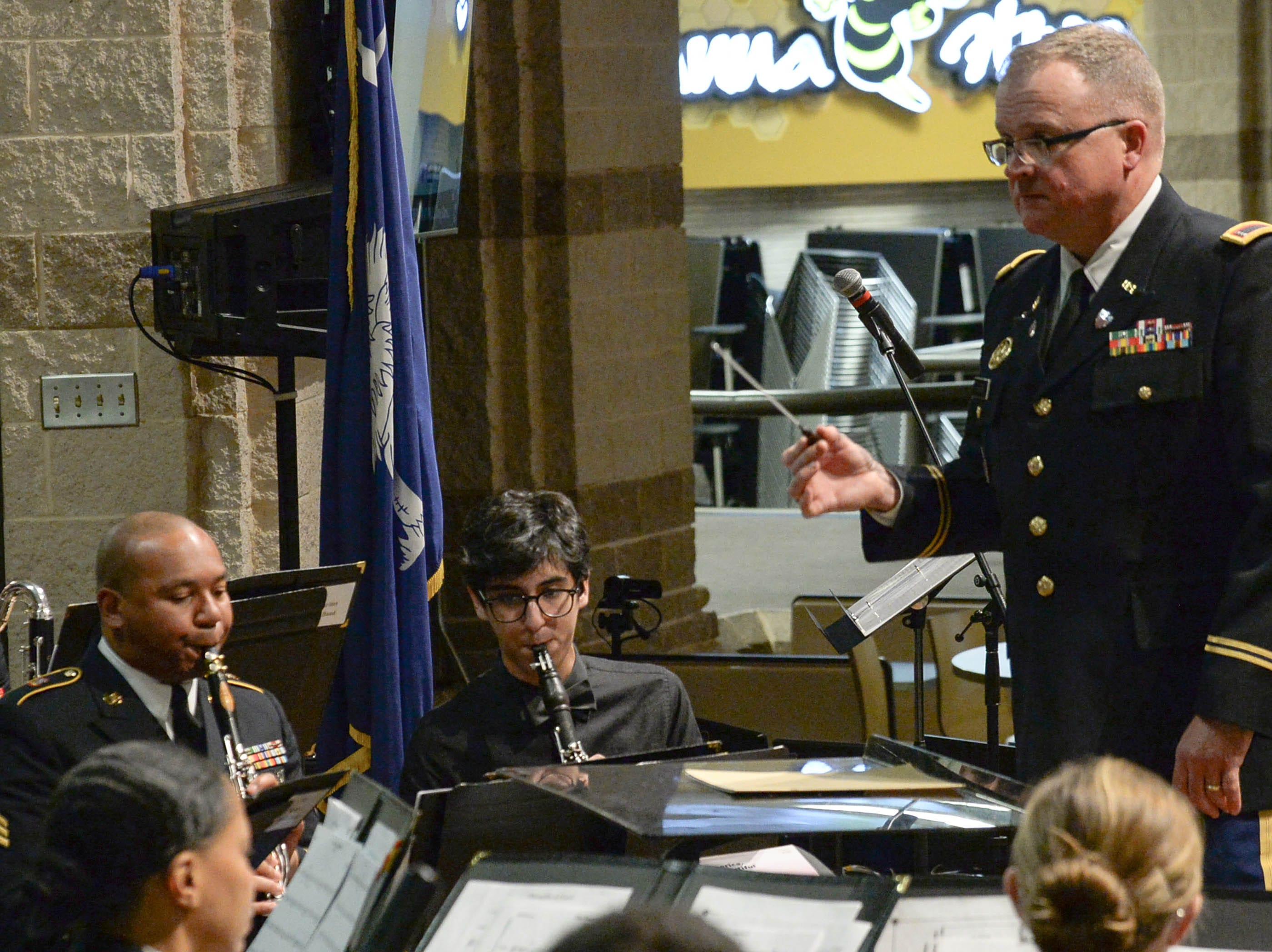 Emilio Becerra, middle, a senior at T.L. Hanna High School in Anderson, plays clarinet for one song near SGT Nigel Brown, left, under the direction of Bandmaster George T. Bauer, right, of the 282d U.S. Army Band, during a free concert at T.L. Hanna High School in Anderson Thursday, March 7.   Bauer, a 1987 D.W. Daniel High School graduate, and the band are visiting high schools in the upper state, where they talk with band class students about band opportunities in the U.S. Army and Columbia's Fort Jackson.