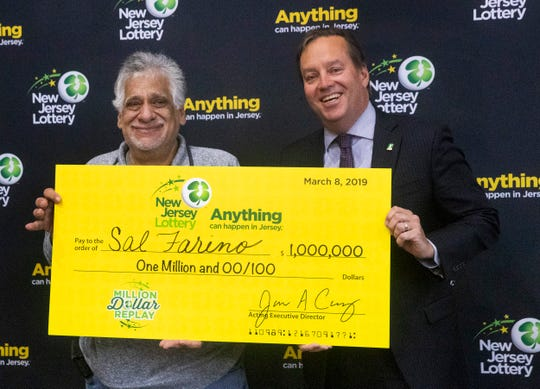 Sal Farino of Clifton holds his 1,000,000 check as he stand with New Jersey Lottery Acting Executive Director James A. Carey, Jr at the drawing at Asbury Park Convention Hall on March 8, 2019.