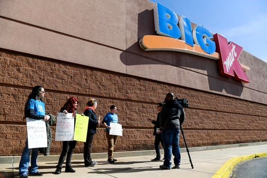 Employees and supporters hold signs at Kmart on Brevard Road as they speak to media March 7, 2019. The store will close its doors Sunday.