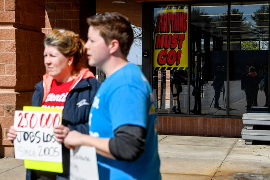 """A sign reading """"Everything must go!"""" hangs in the window as Kmart employee Kimberly Jackson, left, and Gabe Maguire, right, a seven-year Kmart employee, speak to media as they hold signs in front of Kmart in Asheville March 7, 2019."""