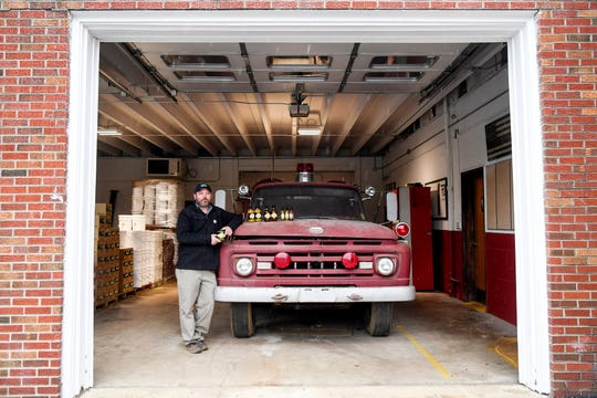 Joel Mowrey, the owner of Smoking J's Fiery Foods, stands next to the Upper Hominy Volunteer Fire Department's first truck, purchased in 1961, with a few of his products at his production facility in Candler March 8, 2019.
