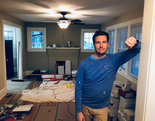 Jason McGill has done a lot of the renovations on his West Asheville home himself, including painting and patching cracks in the plaster.