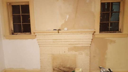 The living room walls have original plaster, but Jason McGill had to fix a lot of cracks and repaint.
