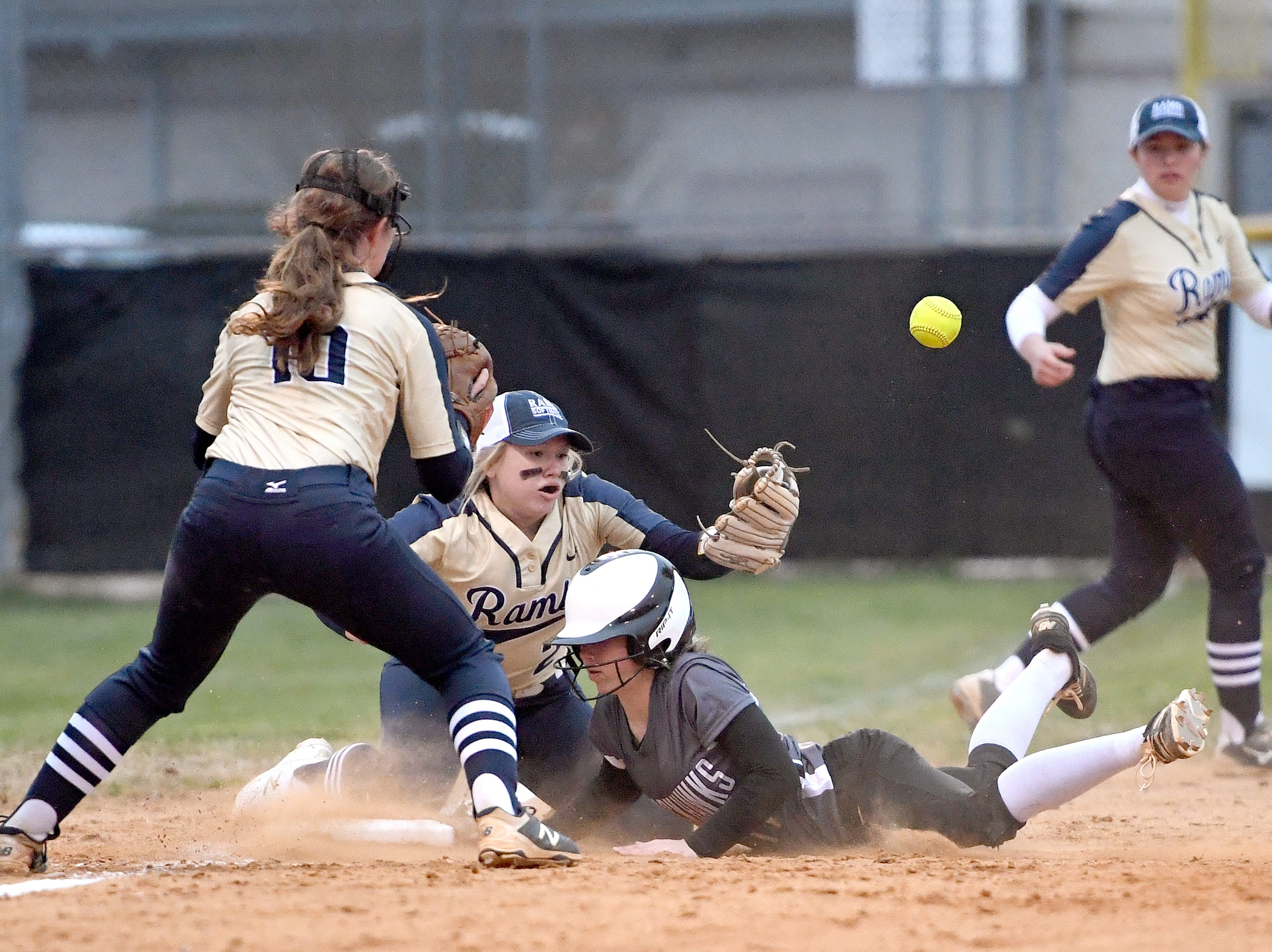 North Buncombe's Riley McCurry slides safely into third base as Roberson's Sydni Owens bobbles the ball during their game at North Buncombe High School on March 7, 2019. North Buncombe defeated Roberson 3-1.