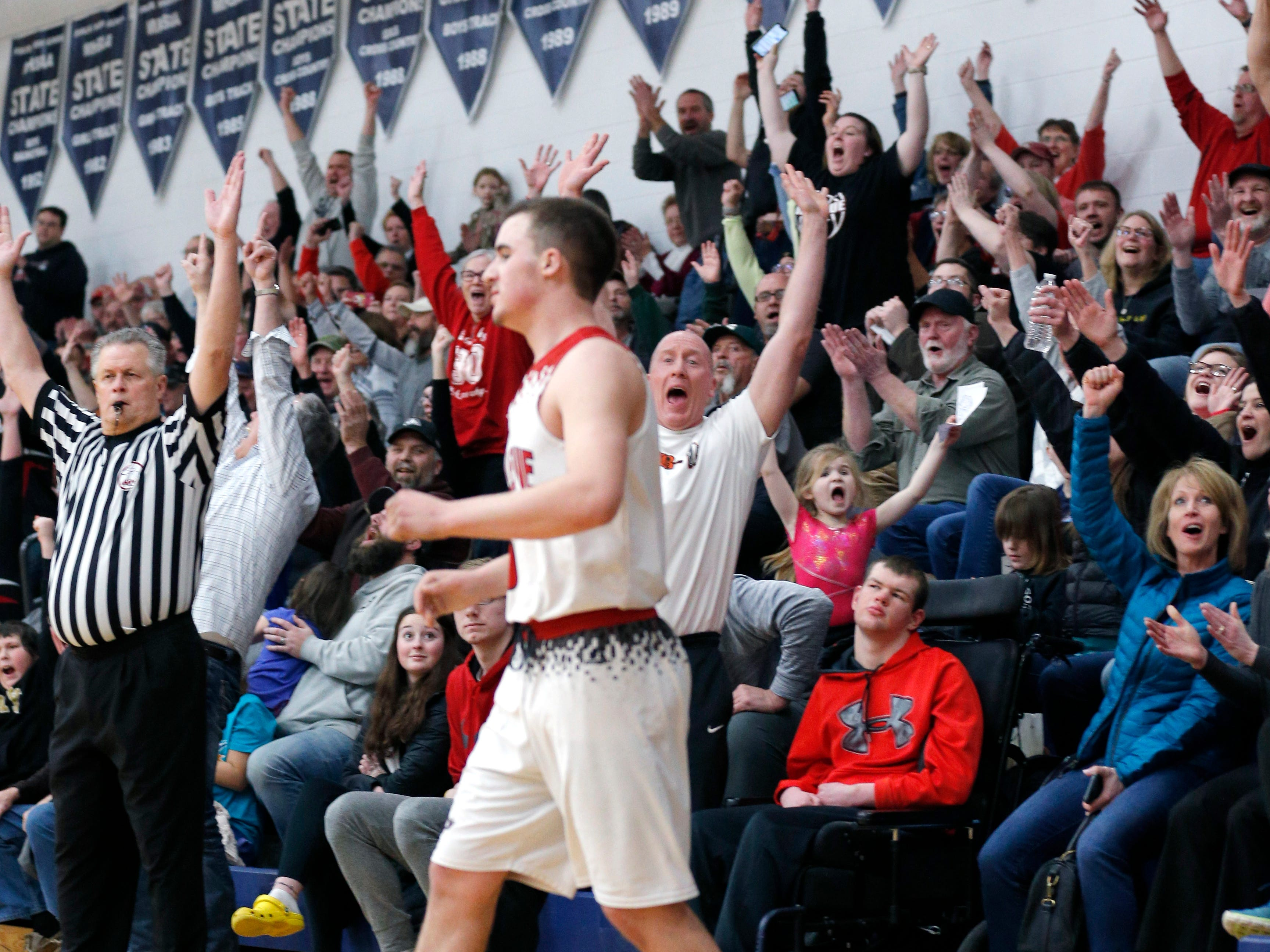 Bellevue fans react after Gino Costello, center, sunk a 3-pointer late in the game against Pittsford in their regional final, Thursday, March 7, 2019, in Fowler, Mich. Bellevue won 42-28.