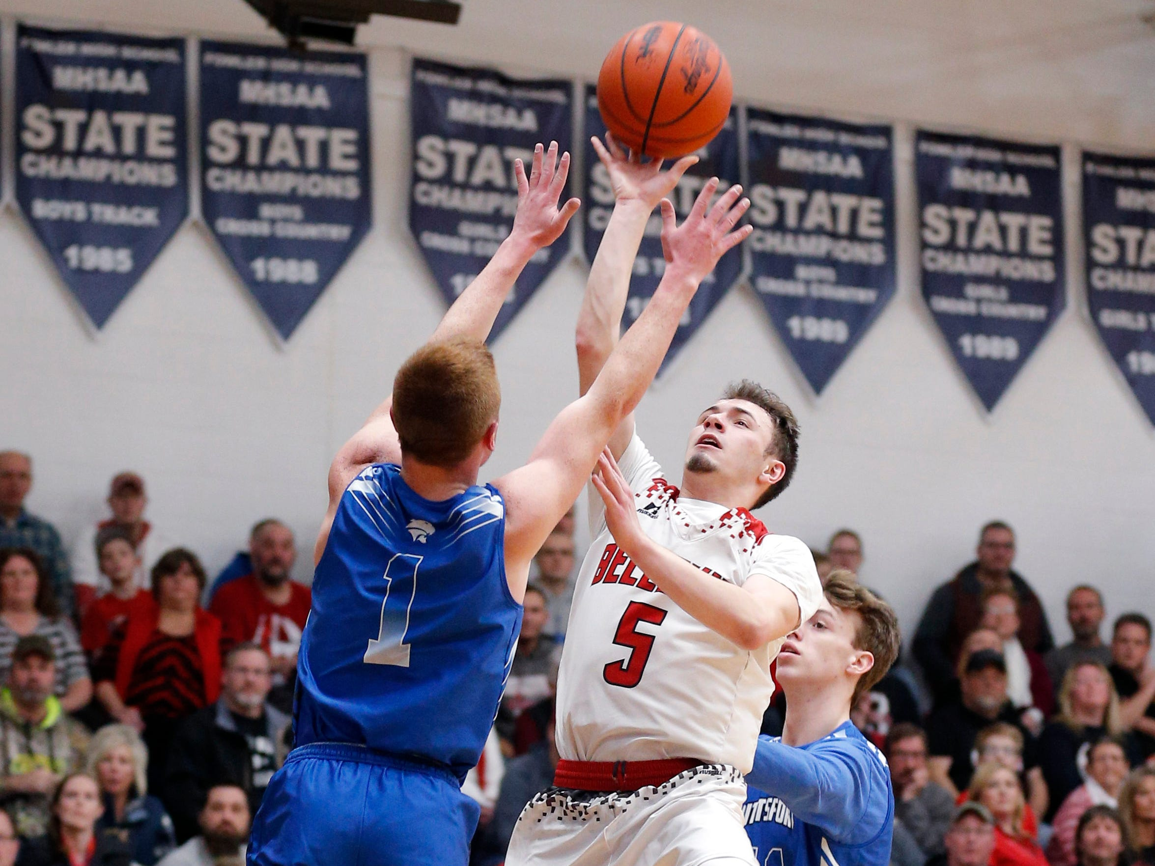Bellevue's Wyatt Waterbury, center, goes up for a shot between Pittsford's Lucas McGraw, left, and Joshua Logan, right, in their regional final, Thursday, March 7, 2019, in Fowler, Mich. Bellevue won 42-28.