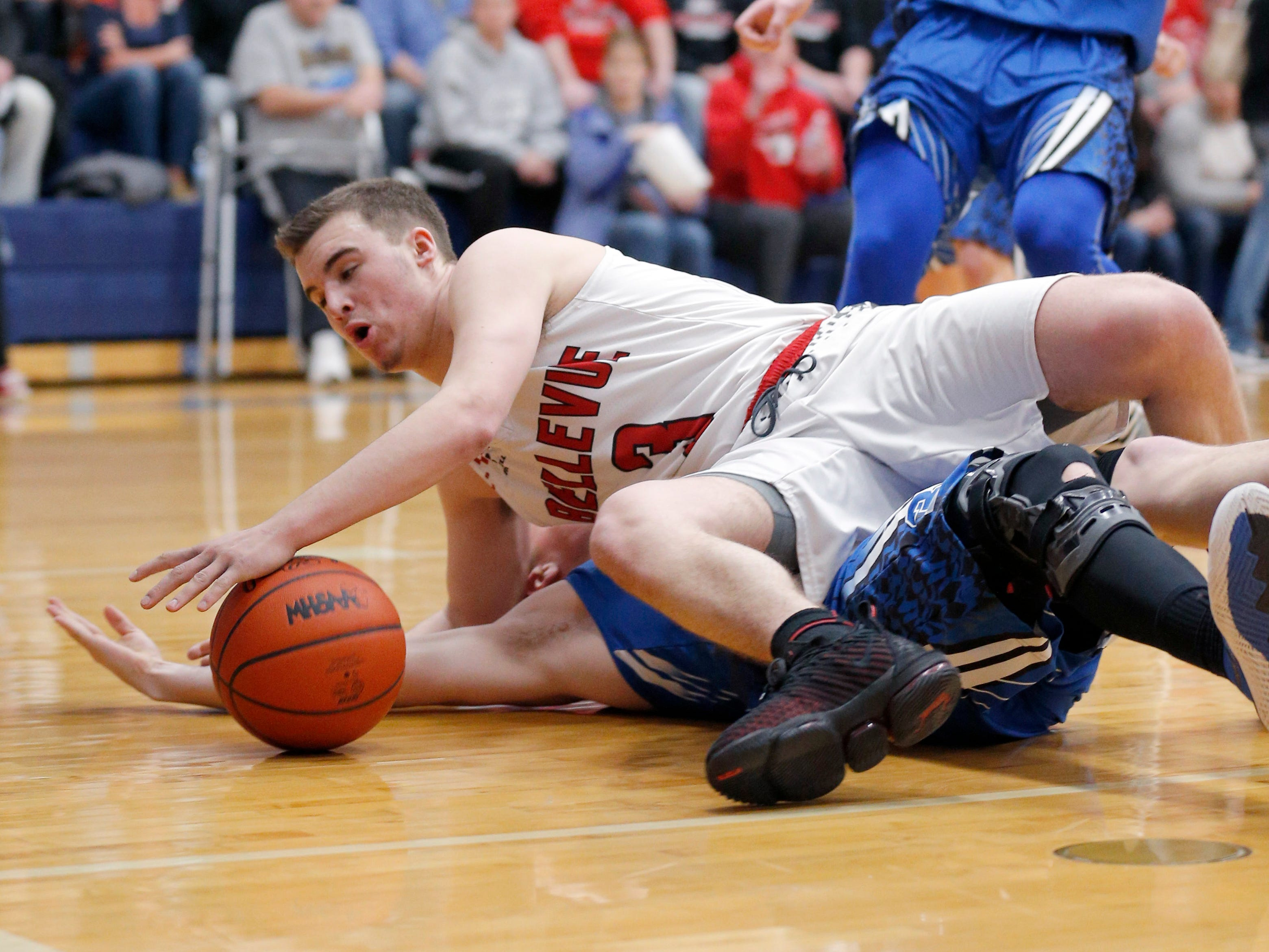 Bellevue's Gino Costello falls on top of Pittsford's Jesse Clement in their regional final, Thursday, March 7, 2019, in Fowler, Mich. Bellevue won 42-28.