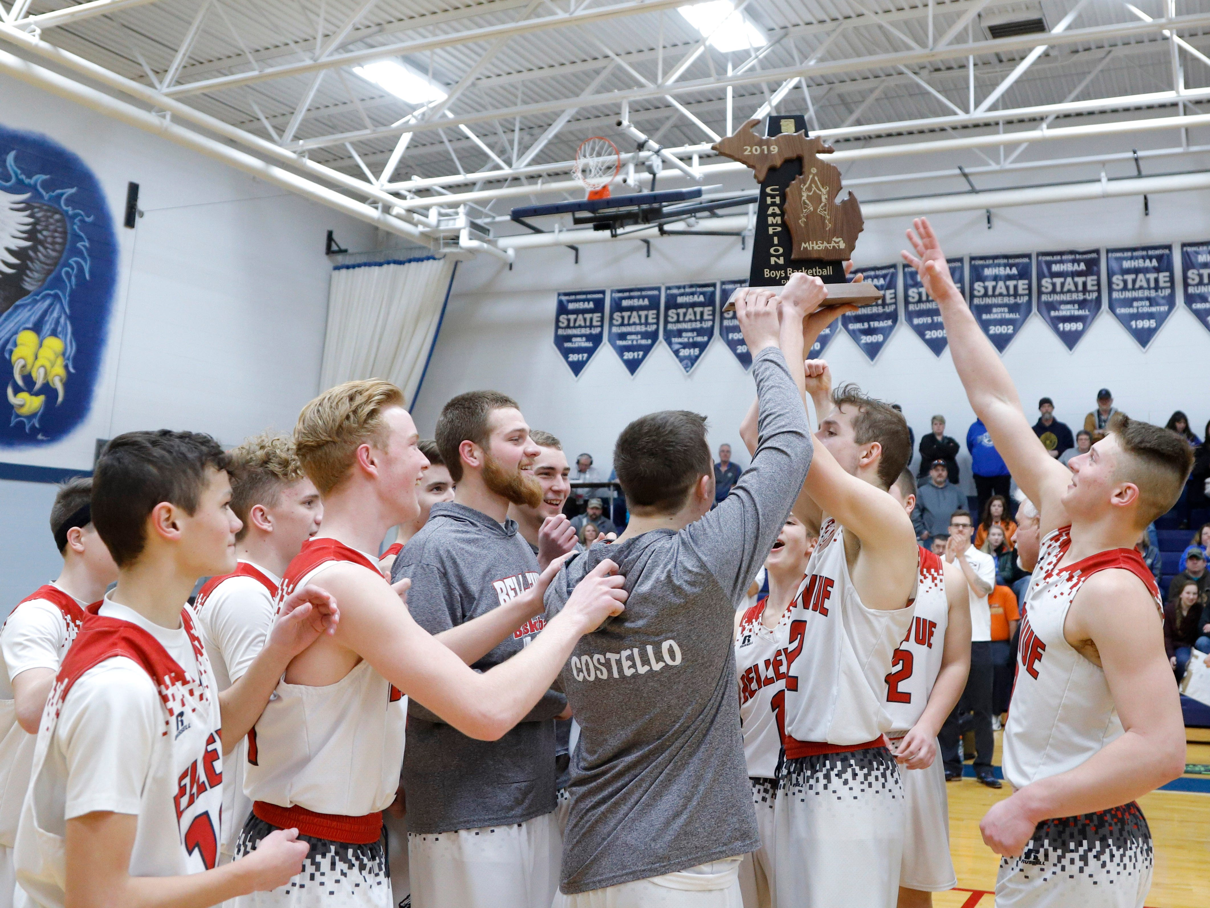 Bellevue players celebrate with their regional championship trophy after defeating Pittsford 42-28, Thursday, March 7, 2019, in Fowler, Mich.