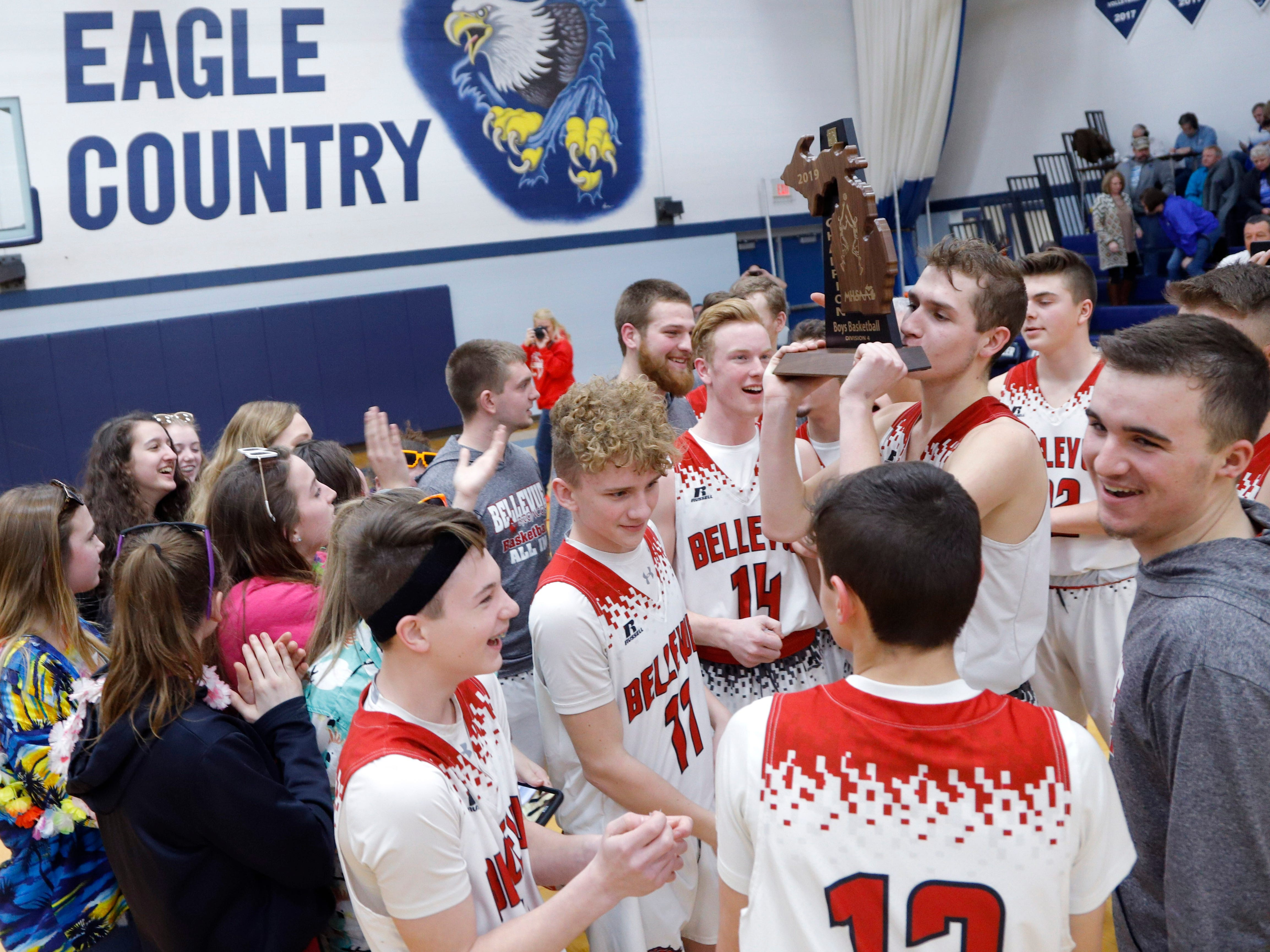 Bellevue players and fans celebrate with their regional championship trophy after defeating Pittsford 42-28, Thursday, March 7, 2019, in Fowler, Mich.