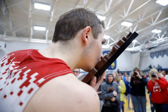 Bellevue's Carter Wing kisses the regional championship trophy, Thursday, March 7, 2019, in Fowler, Mich. Bellevue won 42-28.