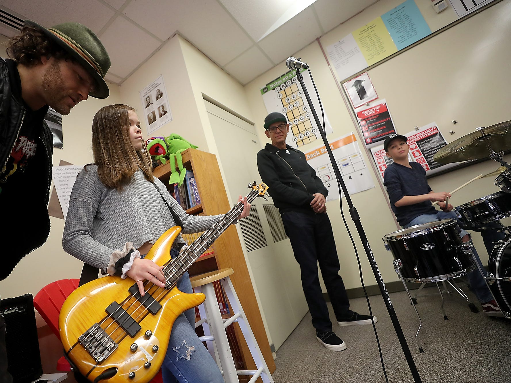 The Lords of 52nd Street bassist Malcolm Gold (left) looks over the shoulder of student Kiyomi McKenzie, 13, and gives her gives her a few pointers as she jams with her fellow student Jaiden Williams (on the drums at right) and the rest of The Lords of 52nd Street band during a visit to Ridgetop Middle School in Silverdale on Friday, March 8, 2019.