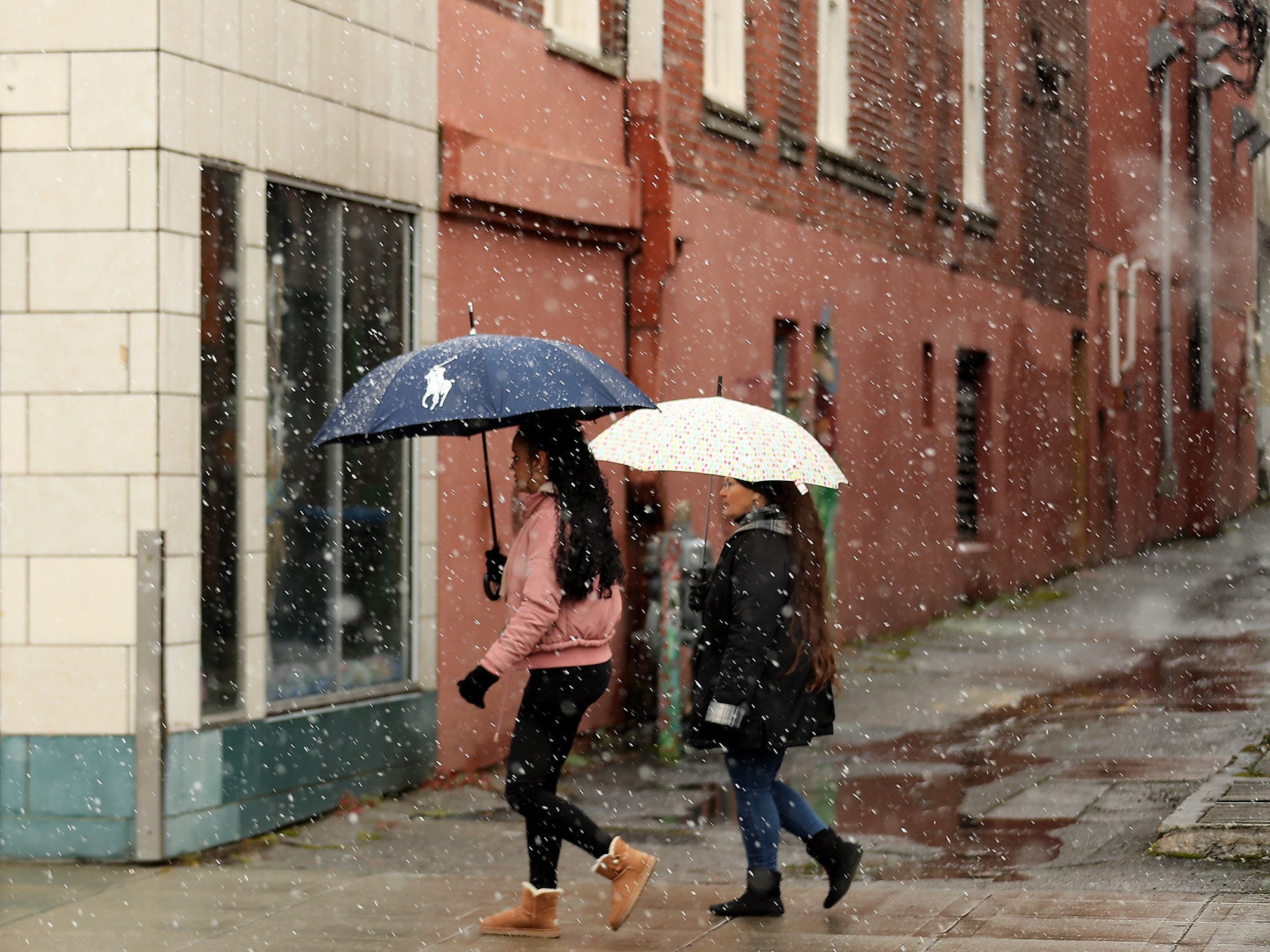 A pair of pedestrians carry umbrellas as the snow falls along Pacific Avenue in downtown Bremerton on Friday, March 8, 2019.