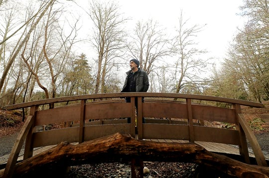Jon Mooallem pauses on the the small foot bridge over the creek as he talks about his walking podcast series at Bainbridge Island's Blakely Harbor Park on Thursday, March 7, 2019.