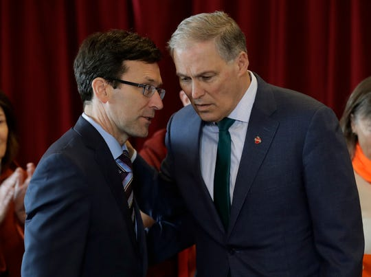 FILE - In this Feb. 14, 2019 photo, Washington Gov. Jay Inslee, right, confers with Attorney General Bob Ferguson, left, at an event in Seattle held by the Alliance for Gun Responsibility. Gov. Inslee and state attorney general Ferguson are urging gun dealers in Washington to abide by the terms of a gun control initiative that was easily passed by voters last November. Inslee and Ferguson, both Democrats, sent a letter Thursday, March 7, 2019, to 262 gun dealers who operate in counties where sheriffs have indicated they will not enforce Initiative 1639. (AP Photo/Ted S. Warren, File)