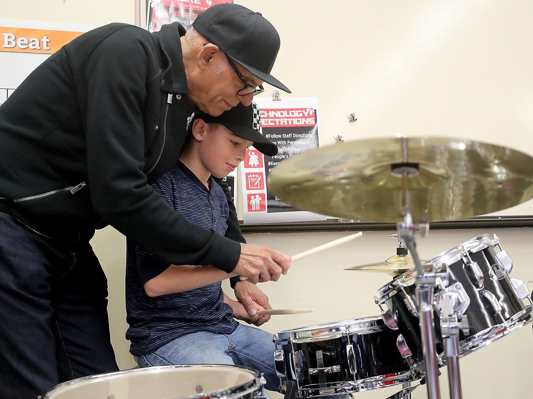 The Lords of 52nd Street drummer Liberty DeVitto gives a few pointers to student Jaiden Williams, 11, during the band's visit to Ridgetop Middle School in Silverdale on Friday, March 8, 2019.