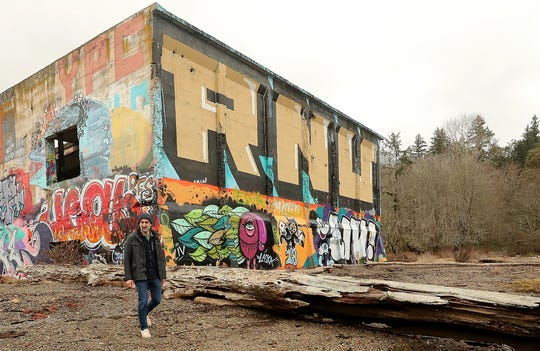 Jon Mooallem strolls past the graffiti covered concrete structure on the shore of Bainbridge Island's Blakely Harbor Park on Thursday, March 7, 2019. Mooallem has created a podcast recording his walks on the island.