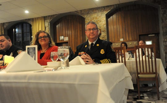 Swannanoa Fire Department Chief Anthony Penland, seated next to his wife Cindy, prepares to deliver a speech at the 100th Annual Black Mountain Fire Department Banquet at Assembly Inn on March 4.