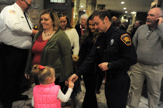 Firefighter Austin Edwards gives a raffle ticket to young girl who was one of the approximately 100 people who attended the 100th Annual Black Mountain Fire Department Banquet on March 4.