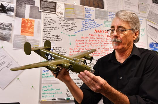 James Cox, secretary of the South Brevard Historical Society, examines a model B-24 bomber in front of his storyboard describing the March 1944 Eau Gallie crash.
