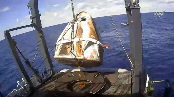 In this image from video made available by NASA, the SpaceX Crew Dragon capsule is hoisted onto a ship in the Atlantic Ocean off the Florida coast after it returned from a mission to the International Space Station on Aug. 2, 2020.