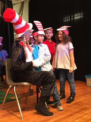 Kindergartners from Tropical Elementary pose for pictures with The Cat in the Hat during a March 1 Dr. Seuss Day celebration at their school.