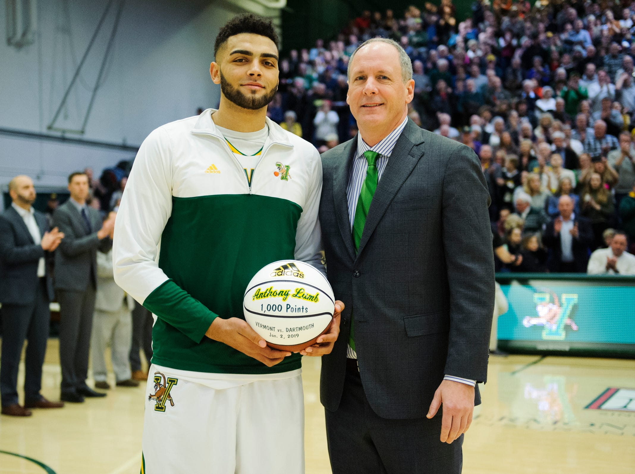 Vermont head coach John Becker presents Vermont forward Anthony Lamb (3) with a ball in honor of scoring 1000 points during the men's basketball game between the Hartford Hawks and the Vermont Catamounts at Patrick Gym on Saturday night January 12, 2019 in Burlington.