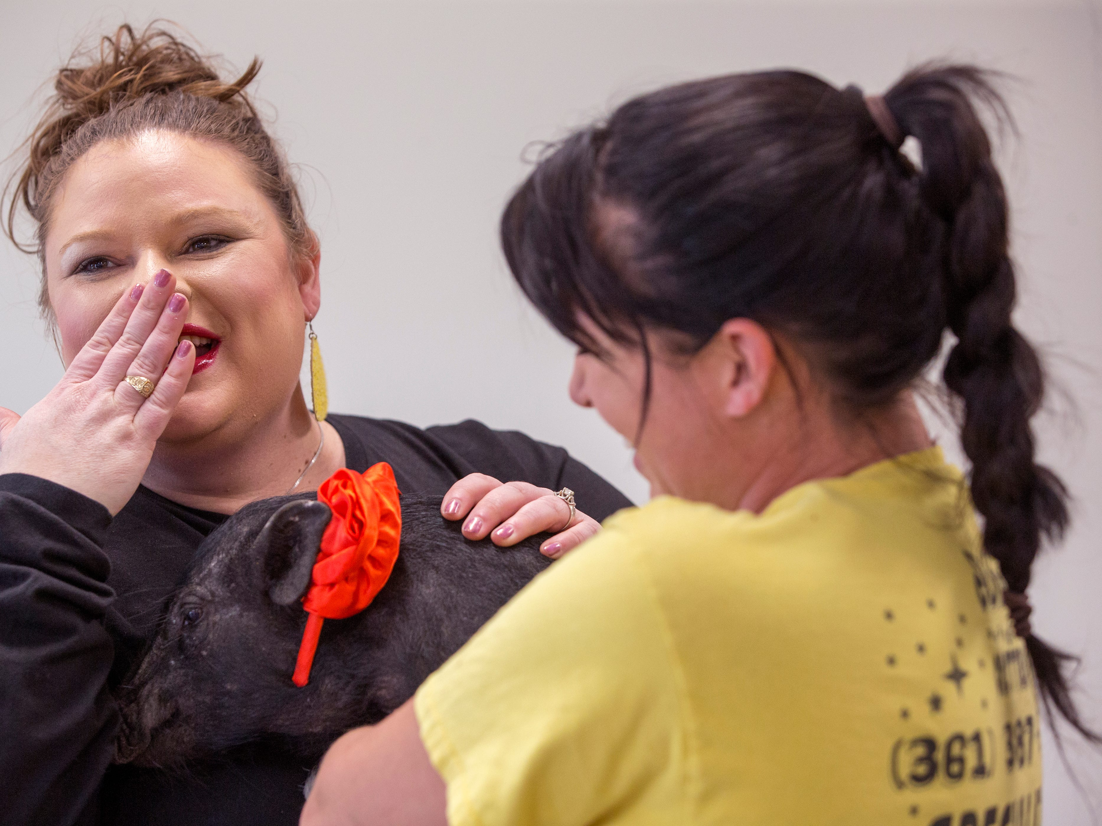 Rise School of Corpus Christi Executive Vanessa Nisbet (left) reacts after kissing Hammy, held by Jonna Rains, on Friday, March 8, 2019. She promised students she would kiss a pig if parents raised over $50,000 at the school's annual 5K, they raised close to $80,000.