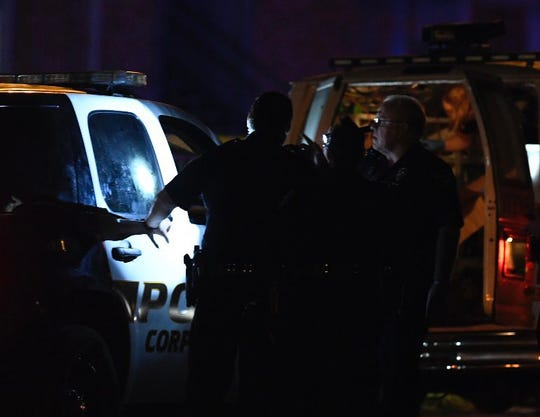 A Corpus Christi police officer shines a flashlight into a police vehicle on Thursday, March 7, 2019. A man is in custody after two women died of apparent gunshot wounds.