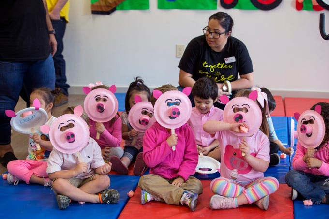 Students at the Rise School of Corpus Christi hold up their pig masks as they wait for their executive director to kiss a pig on Friday, March 8, 2019. She promised she would kiss a pig if parents raised over $50,000 at the school's annual 5K, they raised close to $80,000.