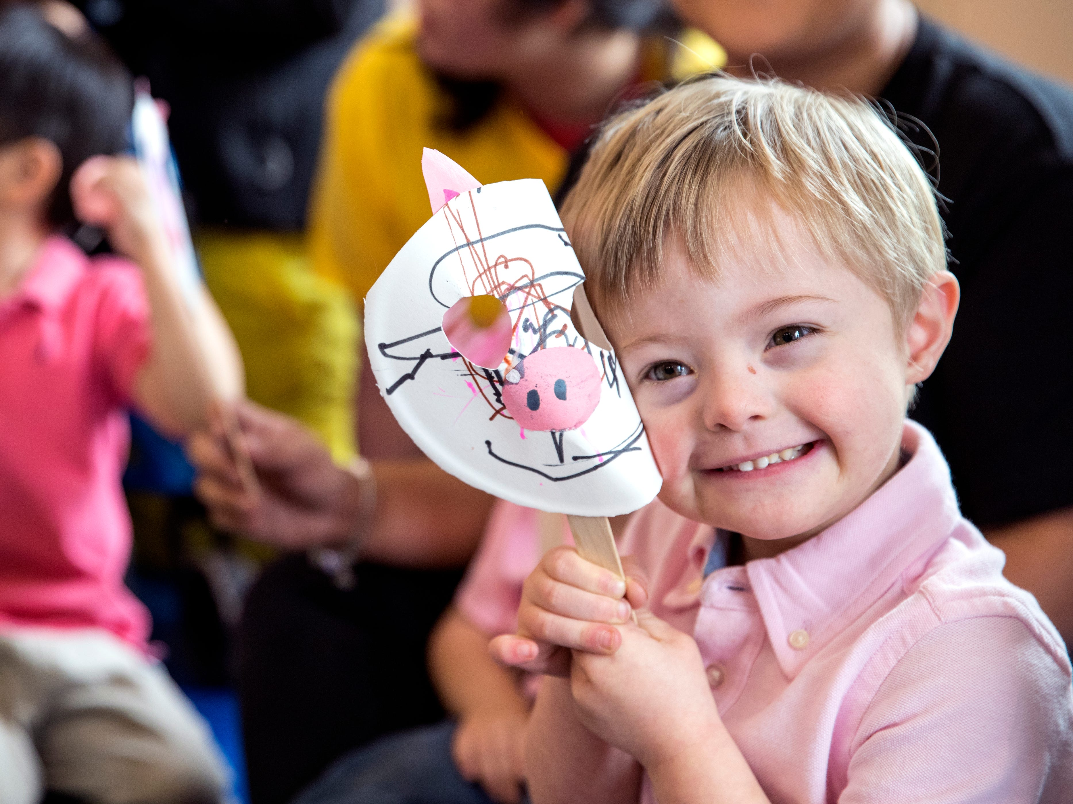 Tres George, 4, a student at the Rise School of Corpus Christi holds his pig mask as he waits for the executive director to kiss a pig on Friday, March 8, 2019. She promised she would kiss a pig if parents raised over $50,000 at the school's annual 5K, they raised close to $80,000.