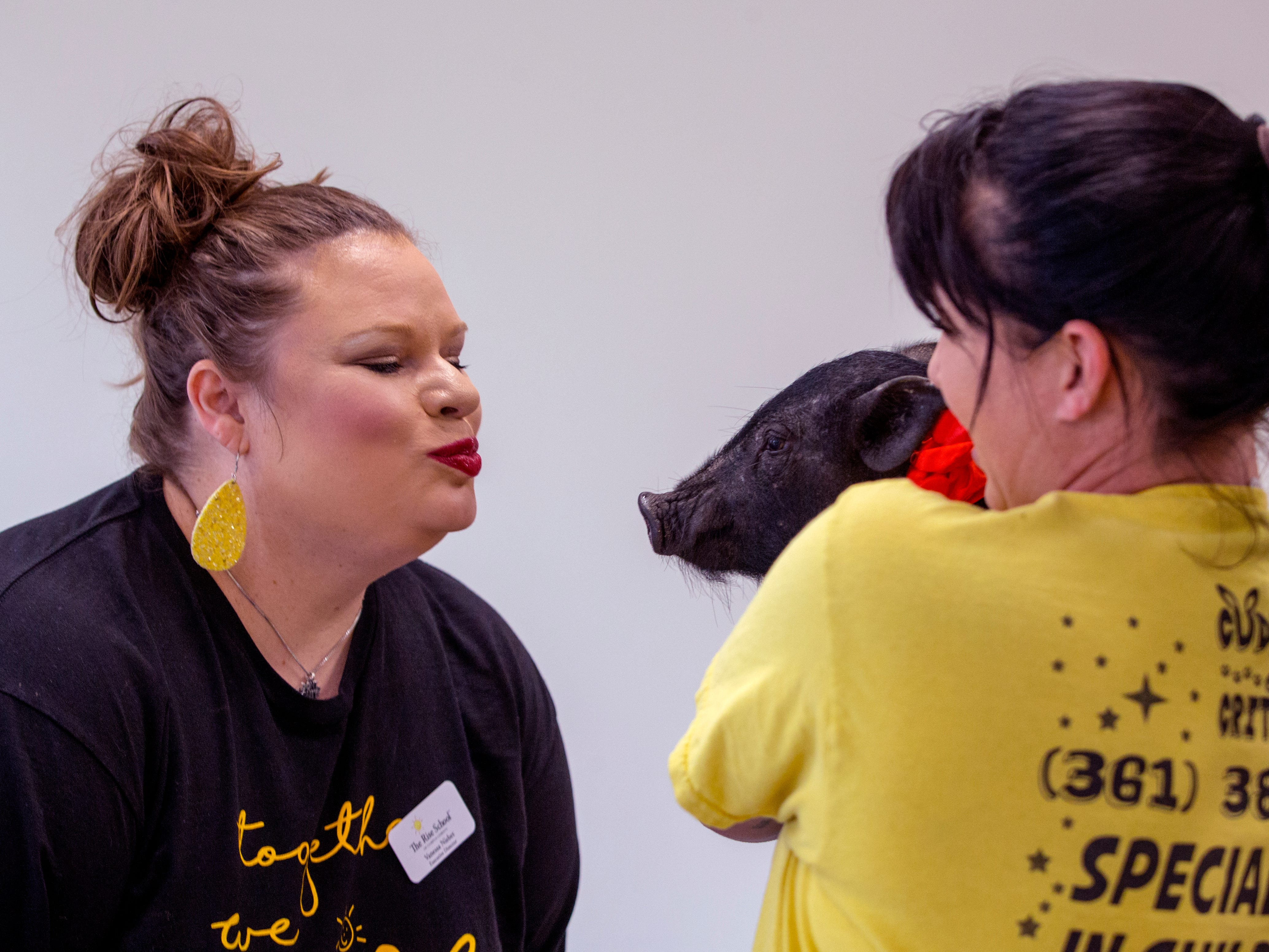 Rise School of Corpus Christi Executive Vanessa Nisbet (left) gets ready to kiss Hammy, held by Jonna Rains, on Friday, March 8, 2019. She promised students she would kiss a pig if parents raised over $50,000 at the school's annual 5K, they raised close to $80,000.