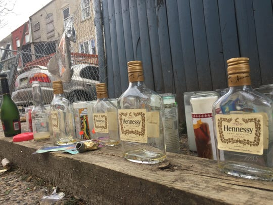 A memorial of liquor bottles and candles marks the scene of a Feb. 15 slaying in an East Camden alley.