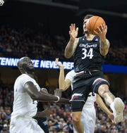 Cincinnati guard Jarron Cumberland (34) charges the basket against Central Florida center Tacko Fall (24) during the first half of an NCAA college basketball game, Thursday, March 7, 2019, in Orlando, Fla.