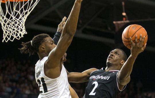 Cincinnati guard Keith Williams (2) tries to shoot over Central Florida forward Chad Brown (21) during the first half of an NCAA college basketball game, Thursday, March 7, 2019, in Orlando, Fla.