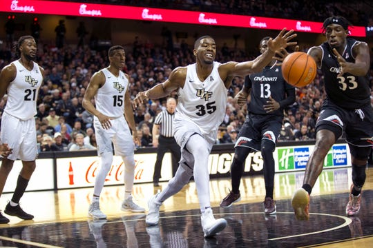 Central Florida forward Collin Smith (35) fights for the ball with Cincinnati center Nysier Brooks (33) during the first half of an NCAA college basketball game, Thursday, March 7, 2019, in Orlando, Fla.