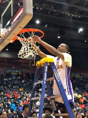 Aiken guard D'Arris Dean cuts down the net at UD Arena Thursday, March 7. Dean scored 32 points in the Falcons' 66-56 win over Alter.
