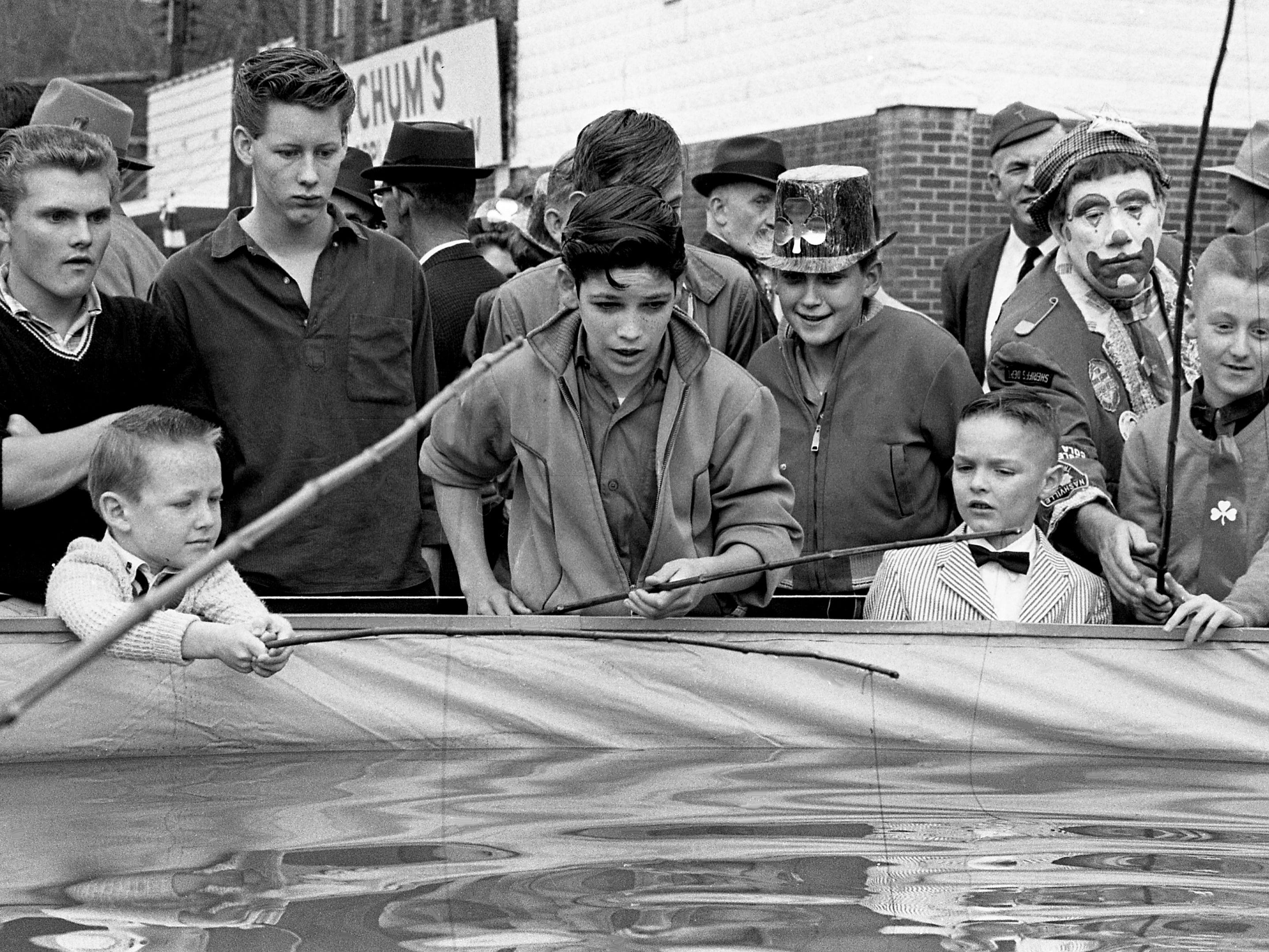 Some youngsters are trying out their luck in the fishing tank set up at the second annual Wearing of the Green celebration in Erin, Tenn. March 14, 1964.