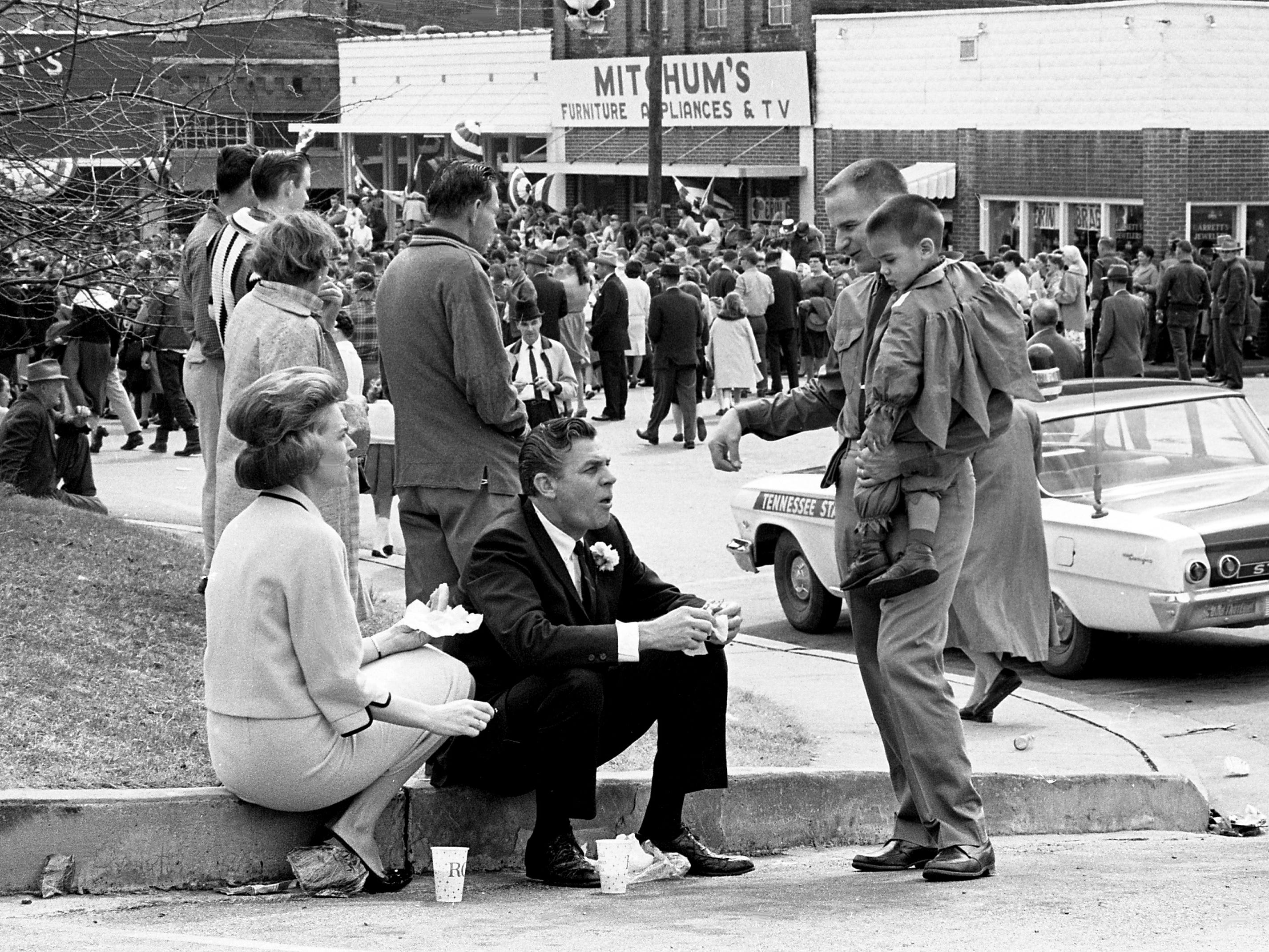 Congressman Ross Bass, center, and wife Avanell, left, share a moment with another as they grab a bite at the end of the parade during the second annual Wearing of the Green celebration in Erin, Tenn. March 14, 1964.