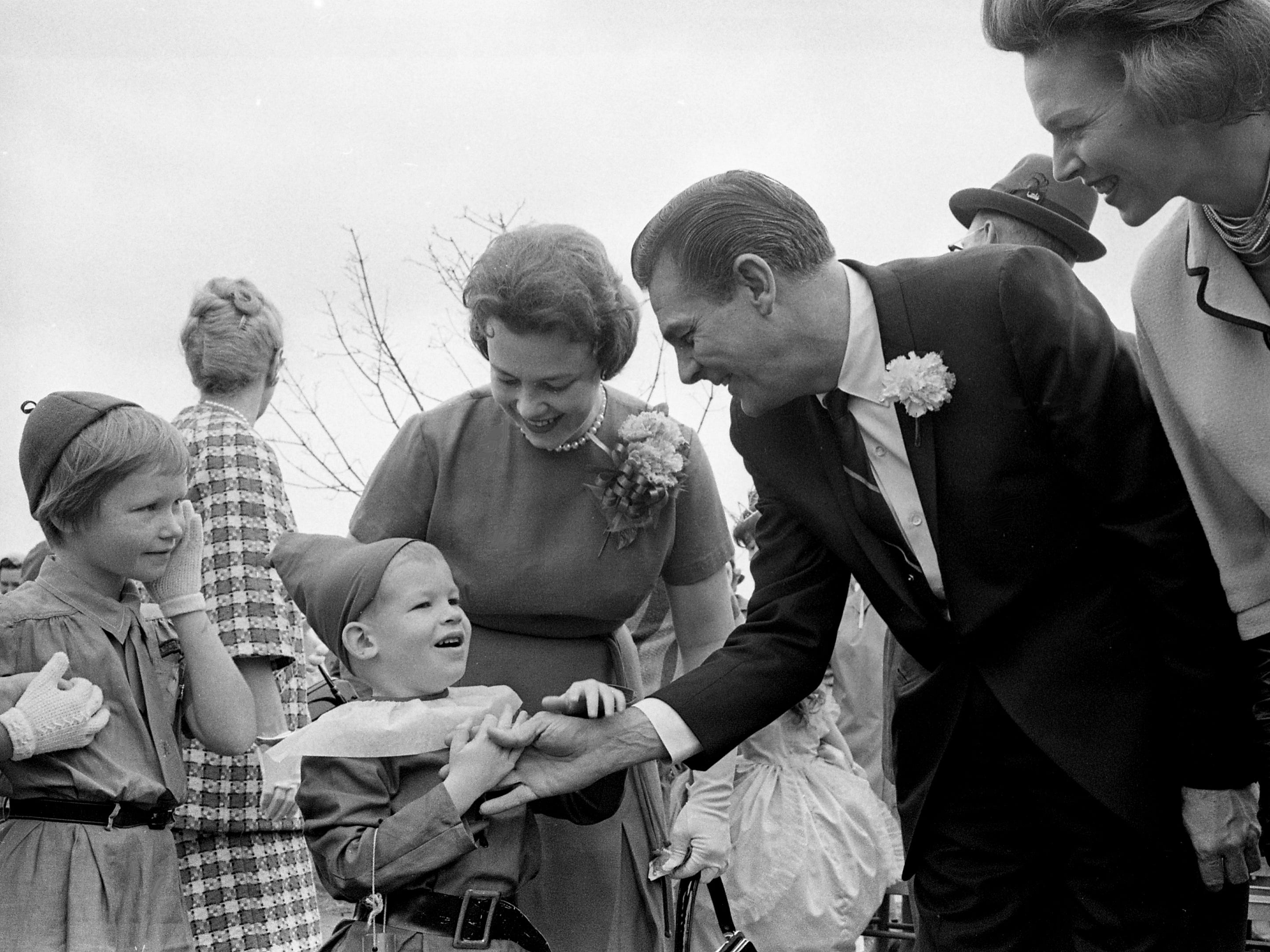 Congressman Ross Bass, center, and wife Avanell, right, share a moment with a young leprechaun after the parade of the second annual Wearing of the Green celebration in Erin, Tenn. March 14, 1964.
