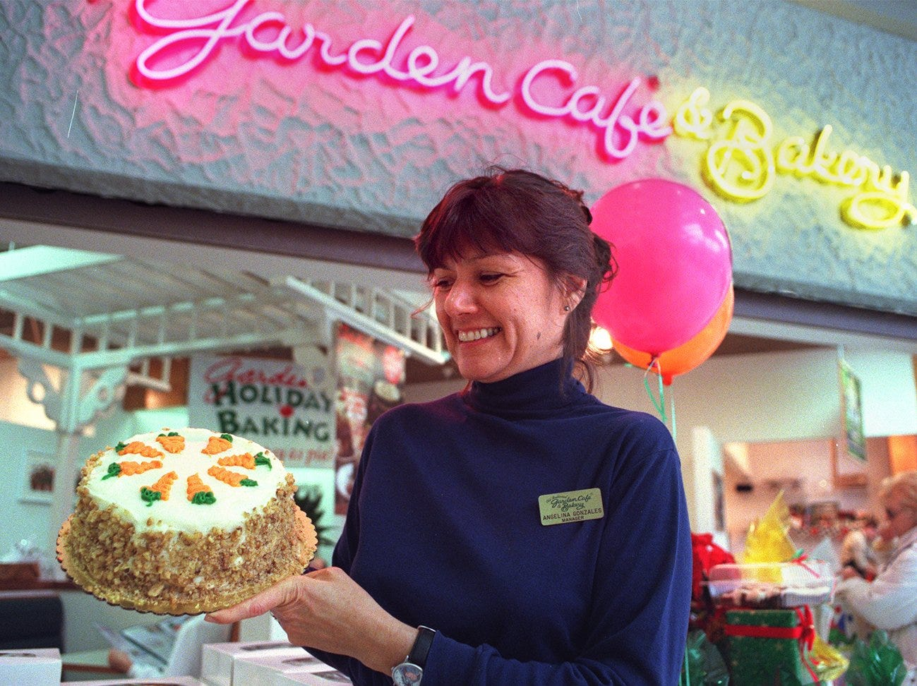 Angelina Gonzales, manager of the Garden Cafe & Bakery at Valley West Mall, with one of her delicious carrot cake desserts on Nov. 26, 1997.