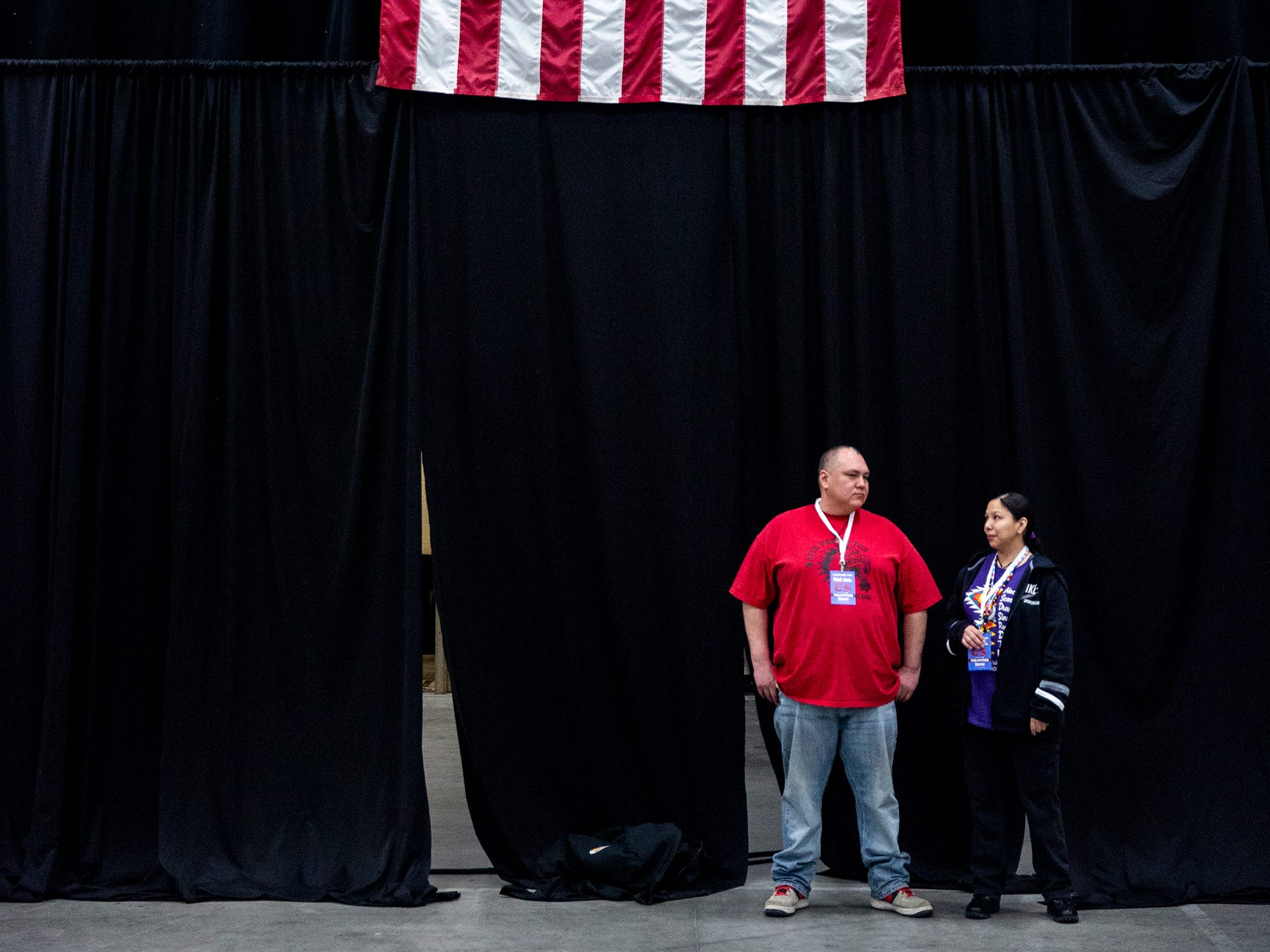 Two volunteers stand under an American flag hung in the Mid-America Center for a rally with Sen. Bernie Sanders, I-VT, on Thursday, March 7, 2019, in Council Bluffs.