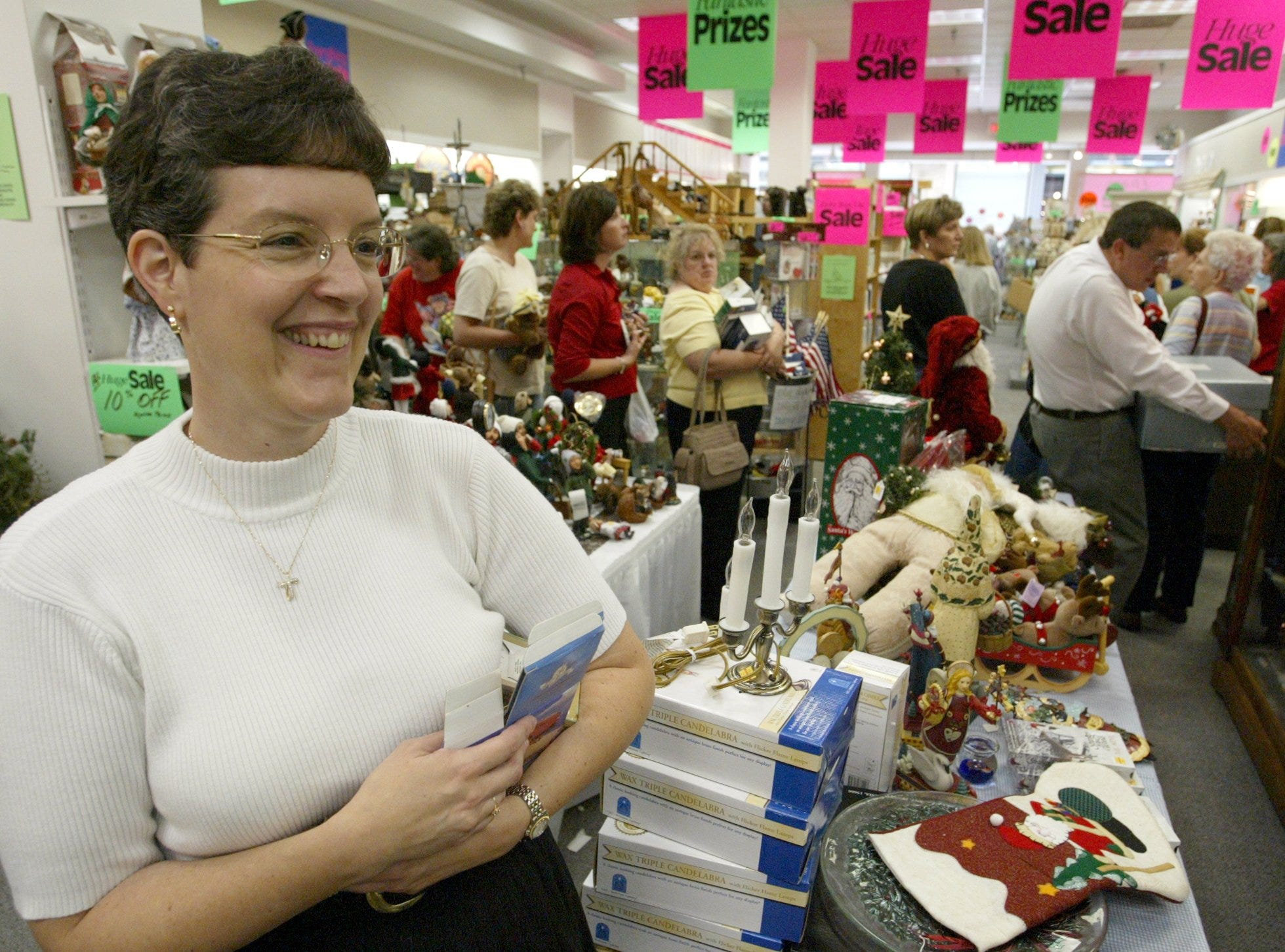 Ellen Harrison, who owns Brodericks Gifts and Collectibles with her husband, Russ, stands in the store July 10, 2003, as shoppers wait in line to purchase their marked-down goods. The Harrisons expect to close the Valley West Mall store in mid-September.