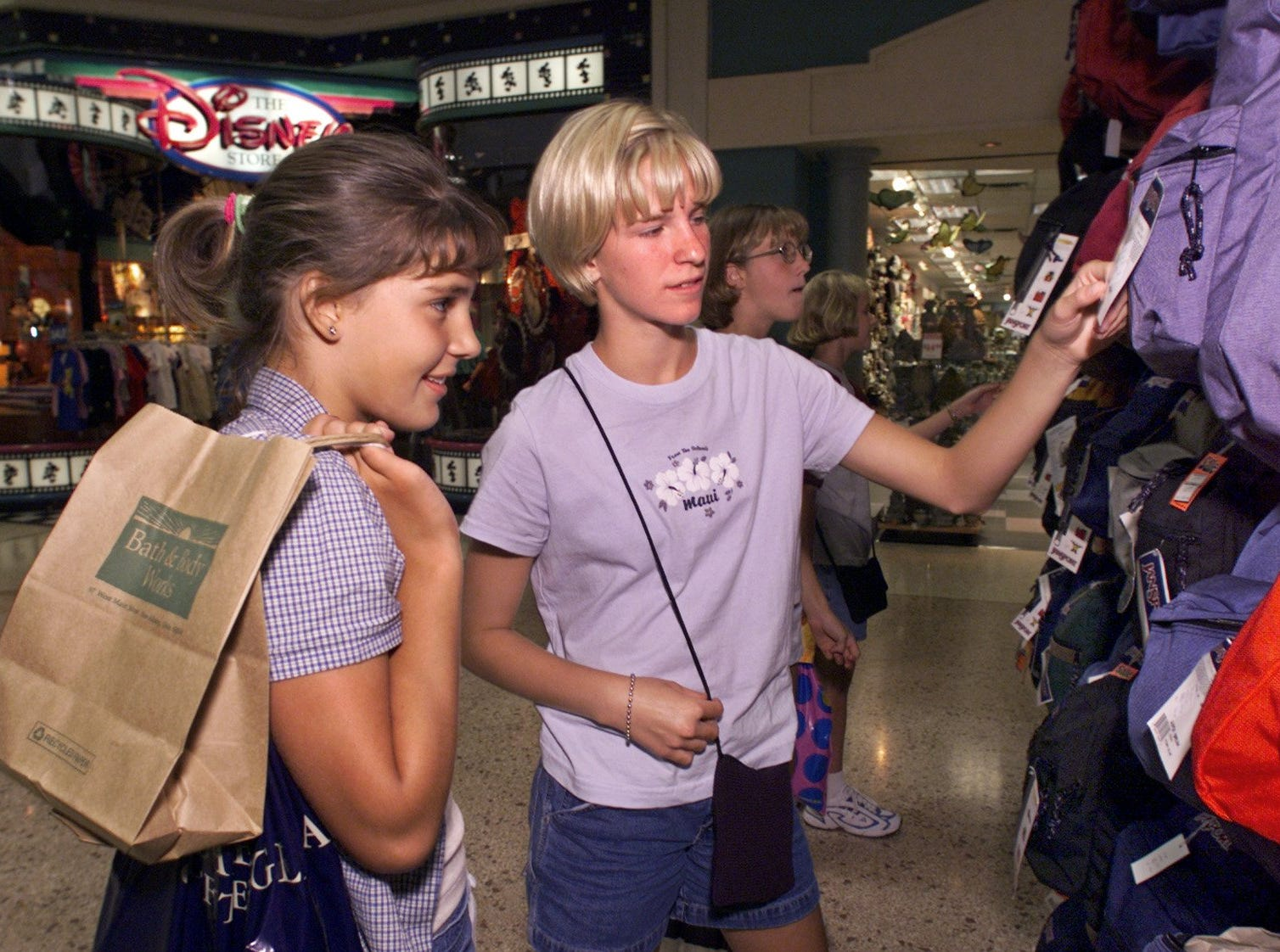 Ashley Brown, left, and Andrea Kinnetz, right, both age 12 from Emmetsburg, look at backpacks while shopping at Valley West Mall. They were down for the day with other friends shopping for school. Photo taken on Aug. 13, 1999.