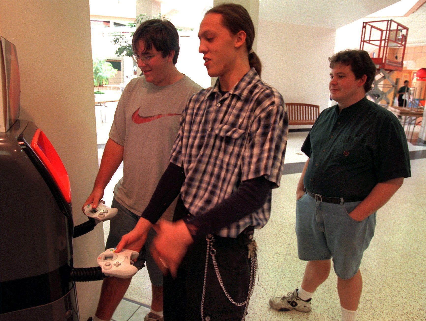 Matt Olson, left, of West Des Moines, and Matt Ziegenfuss, in plaid shirt, play a new Sega Dreamcast boxing game at Babbage's in the lower level of Valley West Mall. The two are both 18-years-old. At right, watching the action on the monitor, is Kevin Cunningham of Des Moines. Shot on Sept. 1, 1999.