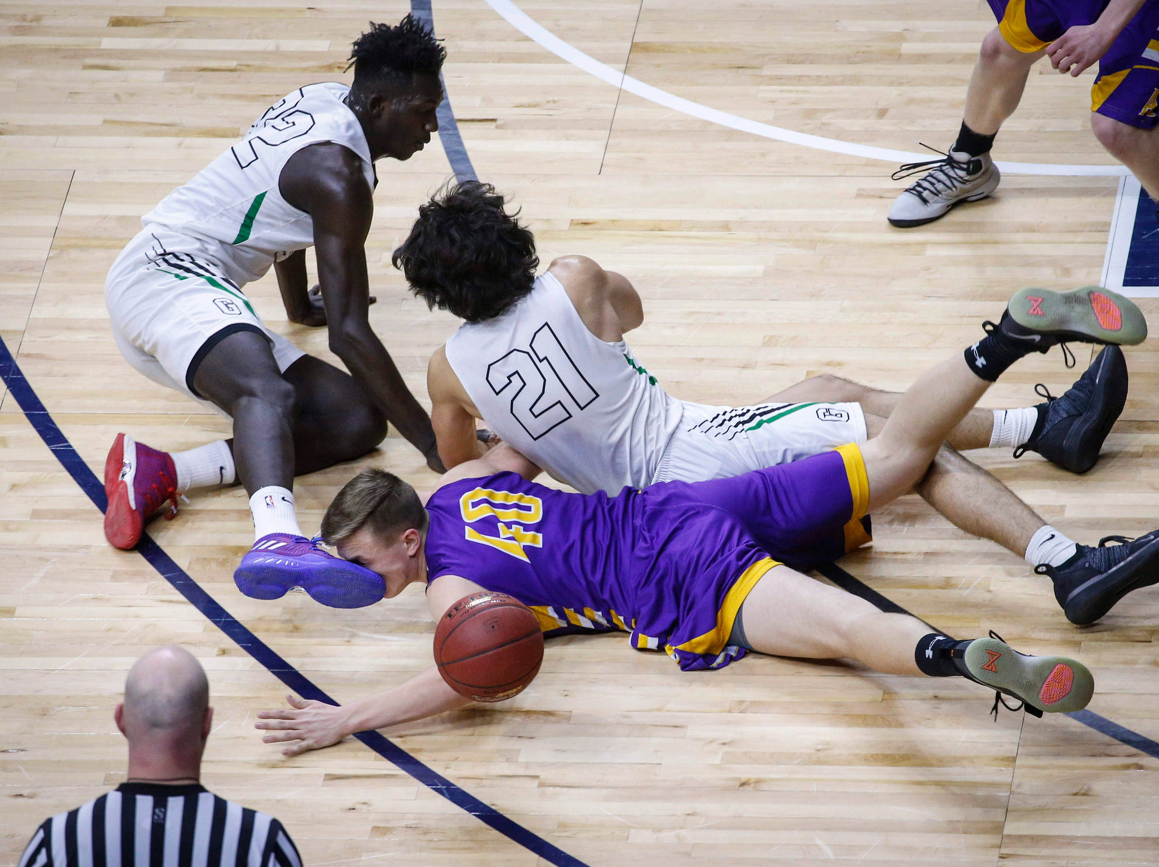 Alburnett sophomore Shane Neighbor gets a face full of Grand View Christian senior Harouna Sissoko's shoe as they scramble for a loose ball in the first quarter during the Class 1A boys state basketball championship game on Friday, March 8, 2019, at Wells Fargo Arena in Des Moines.