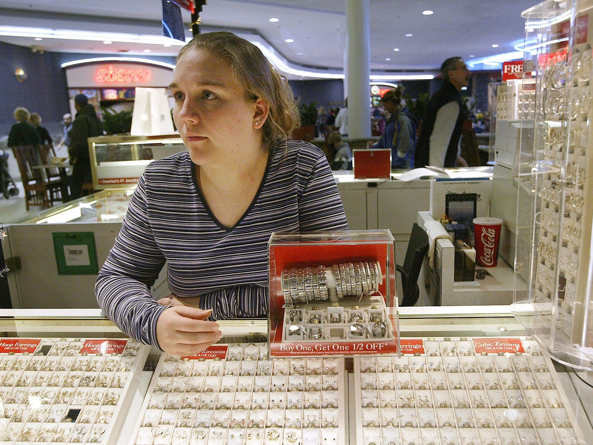 Angela Gray of Des Moines, South, at her job at Piercing Pagoda at Valley West Mall in West Des Moines on Tuesday, Dec. 23, 2003.
